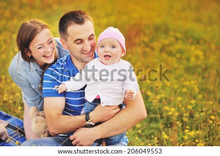 Happy family concept. Mother father and lovely daughter at summer field.