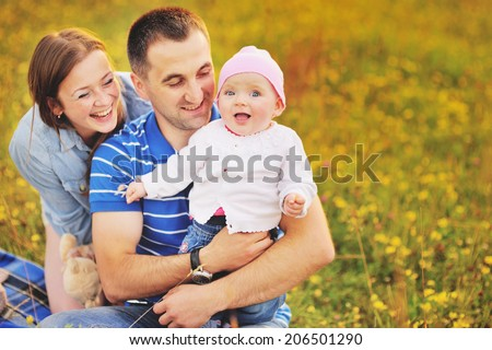 Happy family concept. Parents  and lovely daughter at summer field. - stock photo