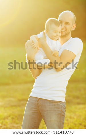 Happy family concept. Portrait of playing father and little son in white casual t-shirts. Toddler in white socks and diaper. Rays of light at summer sunrise. Outdoor shot - stock photo
