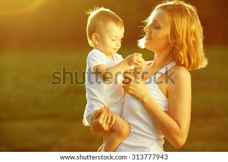 Happy family concept. Portrait of playing mother and little son in white casual sleeveless shirts. Toddler in white socks, diaper holding bottle of water. Rays of light at summer sunrise. Outdoor shot