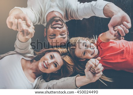 Happy family concept. Top view of happy family of three bonding to each other and smiling while lying on the hardwood floor - stock photo