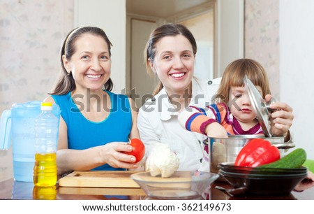 Happy family cook  with vegetables in the kitchen