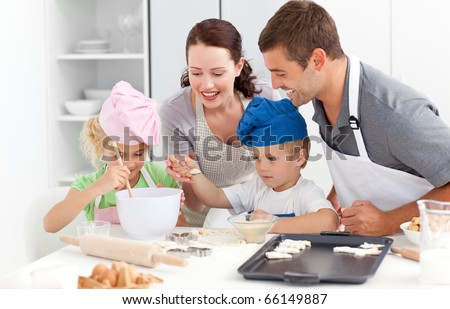 Happy family cooking a cream together in the kitchen while little boy adding sugar in the preparation - stock photo