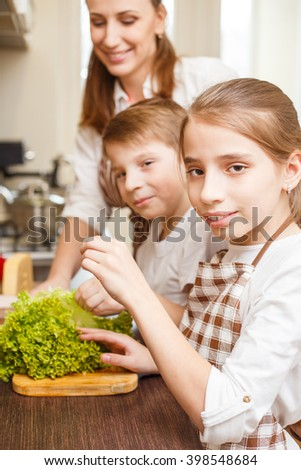 Happy family cooking background. Teenage sister and brother help their mother with cooking salad in the kitchen - stock photo