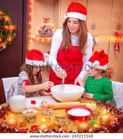 Happy family cooking for Christmas,  mother with two cute kids wearing red Santa hats making festive food on the kitchen, Christmas holidays preparation - stock photo