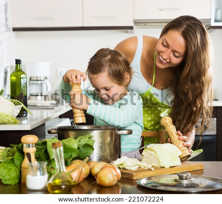 Happy family cooking potatoes soup  at home kitchen - stock photo