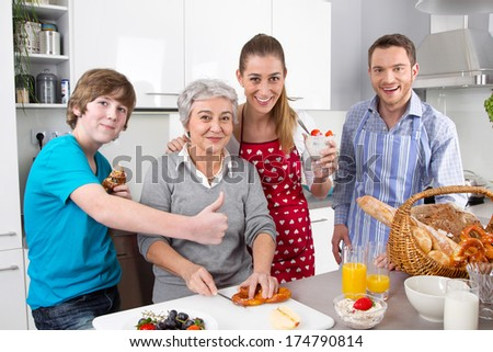 Happy family cooking together - with the grandmother. - stock photo