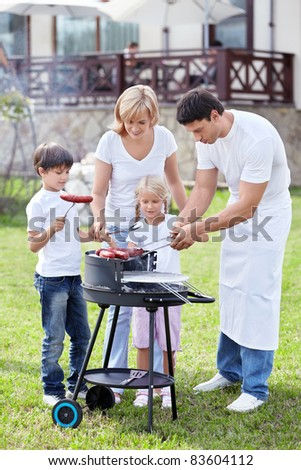 Happy family cooks sausages outdoors - stock photo