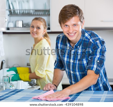 Happy family couple cleaning in the kitchen together and smiling - stock photo