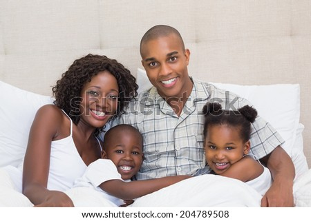 Happy family cuddling in bed together at home in the bedroom - stock photo