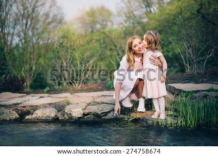 Happy family. Cute daughter kisses her mother near the pond