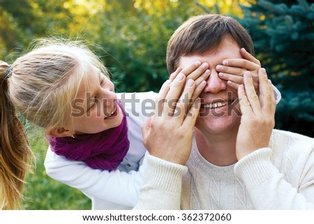 Happy family - Cute girl covers her dad's eyes while playing at the outdoors - stock photo