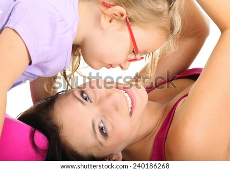 Happy family, cute little girl child playing with mom together having fun. Daughter and mother embracing isolated on white - stock photo