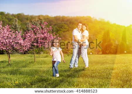 Happy family: cute little girl running in sunset light, her parents hugging on the background