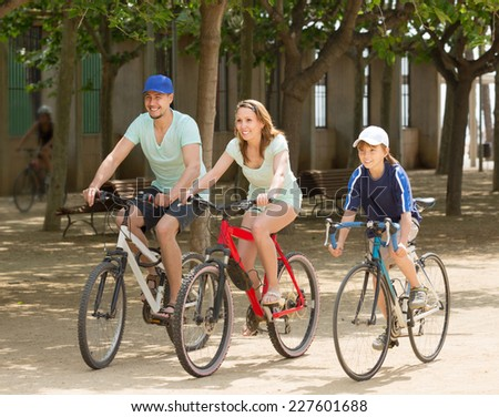 Happy family cycling in park togetherness and smiling - stock photo
