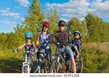 Happy family cycling outdoors. Parents with two kids on bikes - stock photo