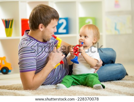 Happy family dad and son play musical toys on floor
