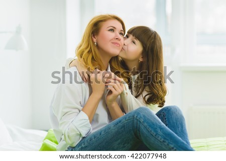 happy family. daughter hugging and kissing her mother indoor - stock photo