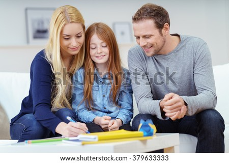 Happy family doing homework together as the parents help their attractive young redhead daughter with her class work on the sofa at home