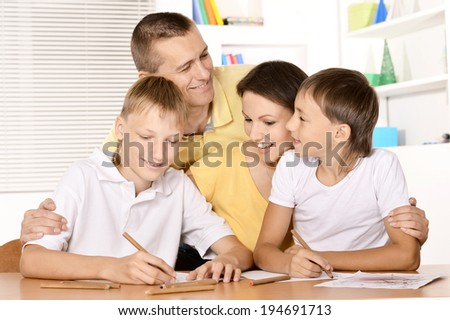Happy family drawing at the table together