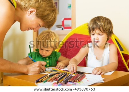Happy family drawing with pencils in home interior