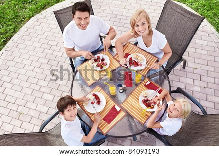 Happy family eating at table - stock photo
