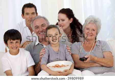 Happy family eating chips and watching television - stock photo