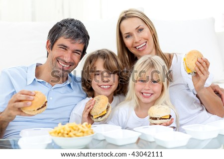 Happy family eating hamburgers sitting on the floor at home