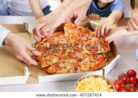 Happy family eating pizza on the wooden table - stock photo
