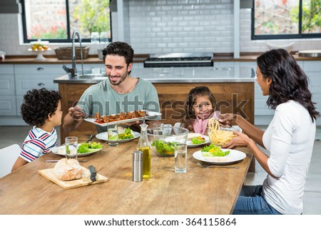 Happy family eating together in the kitchen at home - stock photo