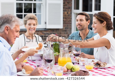 Happy family eating together outdoor. Cheerful woman serving bread to daughter. Smiling generation family sitting at dining table during lunch. Happy cheerful family enjoying meal together in garden.  - stock photo