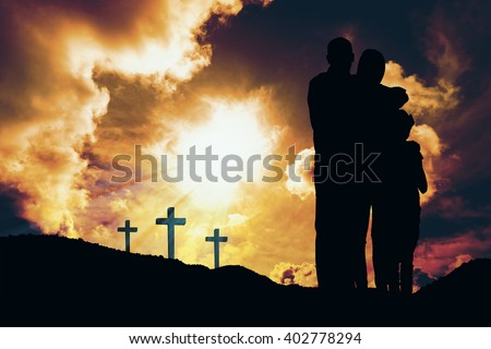 Happy family embracing each other over against cross religion symbol shape over sunset sky