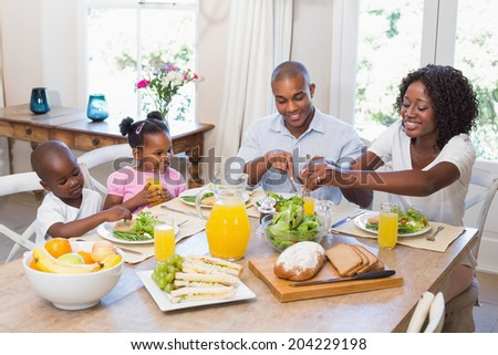Happy family enjoying a healthy meal together at home in the kitchen - stock photo