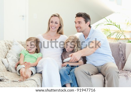 Happy family enjoying a movie together - stock photo