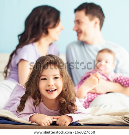 Happy family enjoying a weekend morning together in the bedroom. - stock photo
