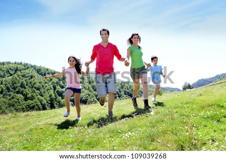 Happy family enjoying and running together in the mountains - stock photo
