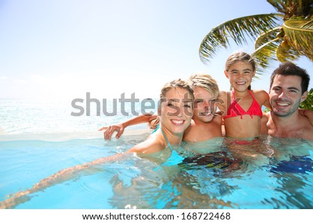 Happy family enjoying bath time in infinity pool - stock photo