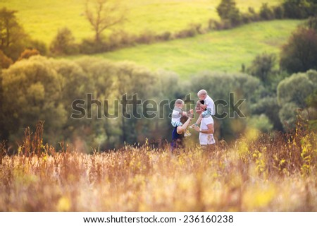 Happy family enjoying life together at meadow outdoor. - stock photo