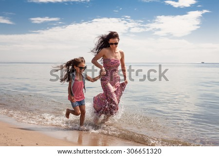Happy family enjoying sunny day at the beach. Mother and daughter - stock photo