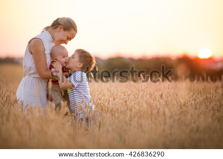 Happy family enjoying sunset in wheat field. Beautiful young woman with adorable baby boy and kid boy. Mother hugging her two children on a meadow on a sunny evening. Mom and sons. Outdoors. - stock photo