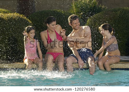 Happy family enjoying together while sitting at the edge of the swimming pool - stock photo