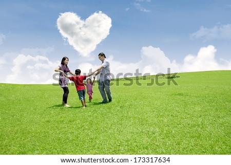 Happy family enjoying valentine in the park - stock photo