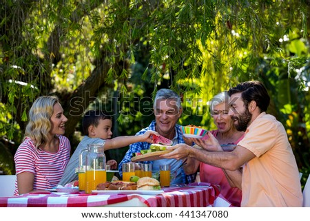 Happy family enjoying while having meal at table in yard - stock photo