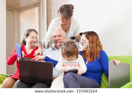 Happy family enjoys on sofa in livingroom room with few laptops   - stock photo