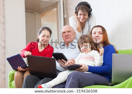 Happy family enjoys on sofa in livingroom room with few various laptops at home - stock photo