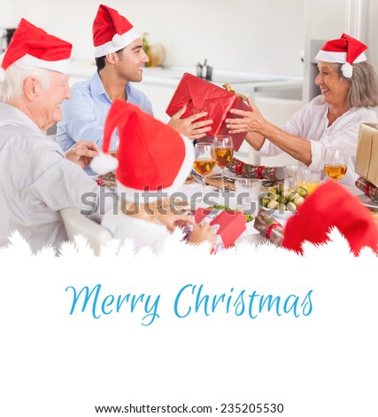 Happy family exchanging christmas gifts against merry christmas - stock photo