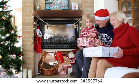 Happy family exchanging christmas gifts in decorated living room with xmas tree and fireplace. Happy loving grandparents giving presents to grandchild. - stock photo