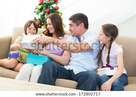 Happy family exchanging Christmas presents at home