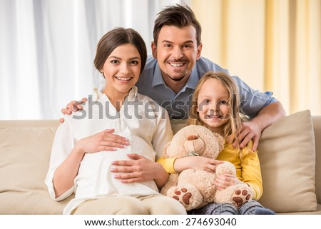 Happy family expecting new baby. They are looking at the camera and smiling. - stock photo