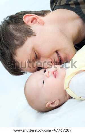 Happy family: father and baby - playing and smiling